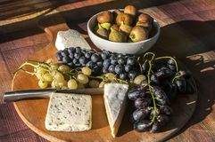 Wooden plateau with grapes and cheese Royalty Free Stock Image