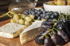 Wooden plateau with grapes and cheese Royalty Free Stock Photos