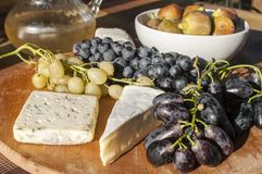 Wooden plateau with grapes and cheese Stock Photo