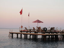 Wooden platform with lounge on sea in turkey. Wooden platform with lounge and flag on sea in turkey Stock Photo