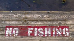 Wooden platform with painted No Fishing sign. Close up shot of a wooden platform with a red and white No Fishing sign painted on its surface in Provo Utah royalty free stock photography