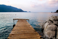 The wooden platform stretching into the sea. Mountains in the background Royalty Free Stock Photo