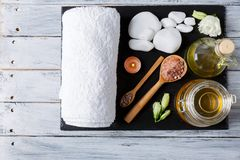 On the wooden platform is a dark board with a bath towel, aroma oil and stones for spa treatments. On the wooden platform there is a dark stone board with a Stock Photo