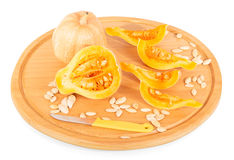 Wooden platter with whole and cut into pieces pumpkin, sunflower seeds. Isolated on white background. stock images