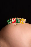 Wooden play blocks spelling the word baby. Pregnant belly with wooden playing blocks spelling the word baby Royalty Free Stock Photo