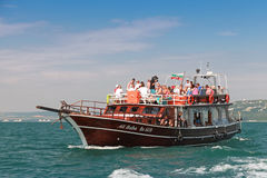 Wooden pleasure boat full with tourists goes on Black sea Stock Image