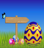 Wooden pointer and Easter eggs Stock Photography