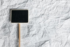 Wooden pointer  lying on a crumpled paper Stock Photography