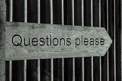 Wooden Pointer Sign with the Word Questions Please Royalty Free Stock Image