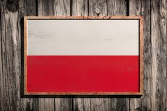 Wooden Poland flag. 3d rendering of Poland flag on a wooden frame over a planks wall Royalty Free Stock Image