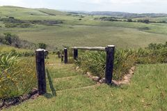 Wooden Pole Barrier Fence Walkway Sugar Cane Plantations Landscape. Wooden pole barrier fenced walkway , green vegetation and sugar cane plantations against stock photography