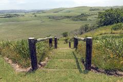 Wooden Pole Barrier Fence Walkway Sugar Cane Plantations Landscape. Wooden pole barrier fenced walkway , green vegetation and sugar cane plantations against stock images