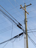 Wooden pole confusing power cable phone line mess. Utility pole hung with confusing and messed-up electricity power cables and telephone lines for residential stock images