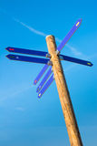 Wooden pole with direction arrows Stock Photo