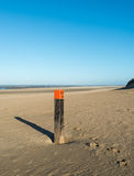 Wooden pole on an empty beach at the North Sea Stock Images