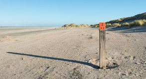 Wooden pole on an empty beach at the North Sea Stock Photos
