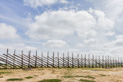Wooden Pole Fence. Roundpole fence dividing cloudy sky and pasture land Royalty Free Stock Photo