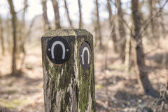 Wooden pole with horseshoe sign royalty free stock photography