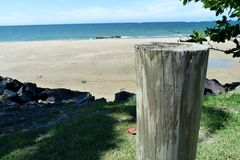 Wooden pole next to the ocean. Wooden pole next to sunny beach in the town of Dorado in tropical Puerto Rico royalty free stock image