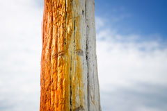 Wooden pole painted orange over the summer sky used for anchoring boats on the seaside Royalty Free Stock Photography
