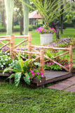 Wooden pole, pathway and flower garden Royalty Free Stock Images