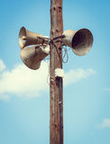 Wooden pole with three speakers Stock Image