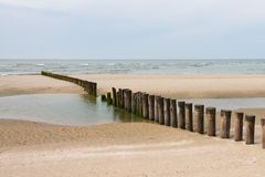 Wooden poles on the beach to break the water. Ameland, the Netherlands royalty free stock photos