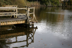 Wooden pontoon. Reflections of wooden pontoon in lake Royalty Free Stock Images