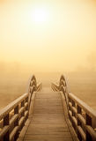 Wooden pontoon bridge in a sunny foggy morning stock images