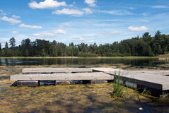A wooden pontoon pier on a forest lake, Marinette County, Wisconsin. A wooden pontoon pier on a lake in summer sunny day, Marinette County, Wisconsin, USA stock photography