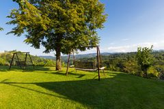Wooden porch swing in garden with view of vineyard in Austria. Summer in Europe royalty free stock image
