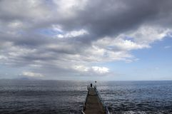 Wooden port pier with fisherman silhouette on the end, wild ocean with waves. Funchal, Madeira, Portugal Royalty Free Stock Photo