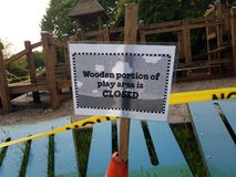 Wooden portion of play area is closed sign and play structure stock photos