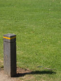 Wooden Post. A wooden post with yellow tape casting a shadow onto grass Royalty Free Stock Image
