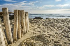 Wooden post on the beach leading ti the sea , blue sky with clouds, stock photography