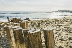 Cloesup of wooden poles, standing at the beach , leading to the. Wooden post on the beach leading ti the sea , blue sky with clouds royalty free stock photos