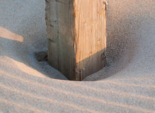 Wooden post buried in the sand Stock Image