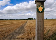 Empty footpath seen near a harvested field in summer, showing a footpath direction. The wooden post in the foreground gives directions for this nature trail Stock Images