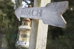 Wooden post with lantern and arrow reading 'beach' Royalty Free Stock Photo