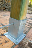 Wooden Post with Metal Support. A wooden fence post fixed to the ground by a riveted metal casing Stock Image