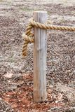 Wooden post with rope tied around it - end of rope fence - dead leaves on ground stock photos