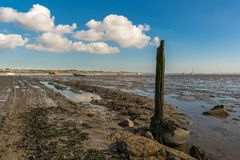 Oare Marshes, England, UK. A wooden post with some clouds, seen at the Oare Marshes near Faversham, Kent, England, UK - with some boats and the Isle of Sheppey royalty free stock image
