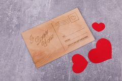 A wooden postcard with red hearts royalty free stock photo