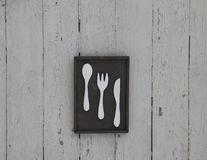 Wooden poster for kitchen with spoon, fork and knife, on the whi Royalty Free Stock Photos