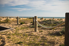 Wooden posts poles with rope in sunset on a sandy beach with atlantic ocean. Algarve, portugal Royalty Free Stock Photos