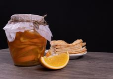 On a wooden pot stand with orange syrup next to a plate of pancakes and orange slices royalty free stock photo