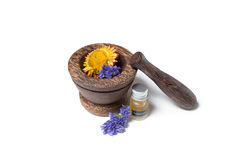 Wooden pounder with bottles of organic oils and flowers Royalty Free Stock Photos