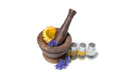 Wooden pounder with bottles of organic oils and flowers Royalty Free Stock Photo