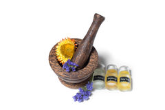 Wooden pounder with bottles of organic oils and flowers Royalty Free Stock Images