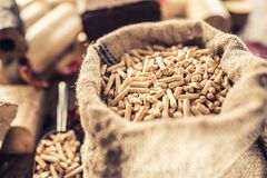 Wooden pressed pellets and briquettes from biomass. Wooden pressed pellets and briquettes from biomass with autumn leaves royalty free stock image